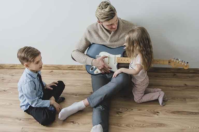 Hombre tocando guitarra con niños