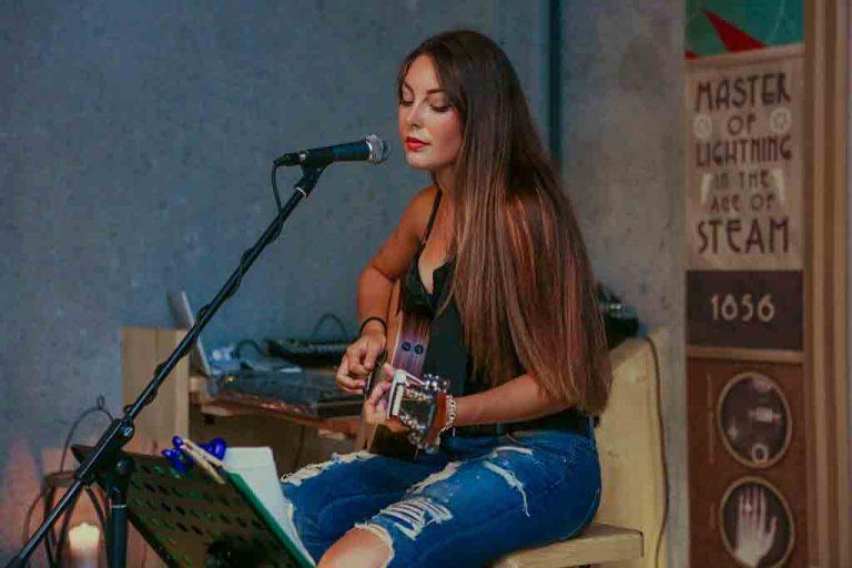 Chica joven tocando la guitarra acústica