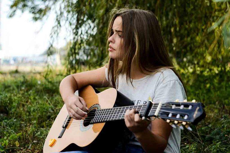 Chica joven tocando la guitarra al aire libre