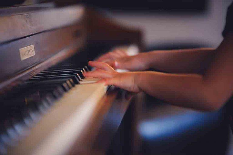 Manos infantiles tocando el piano